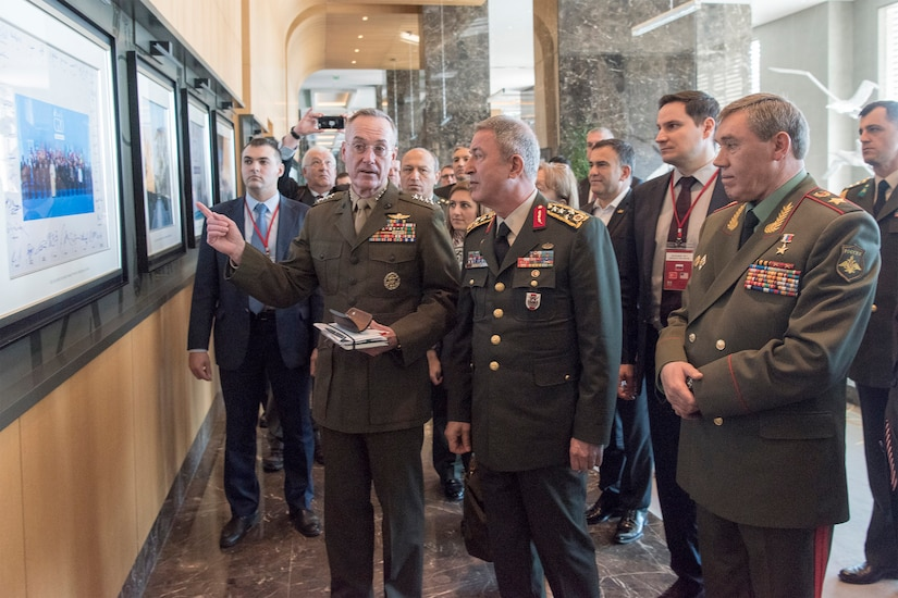 Marine Corps Gen. Joe Dunford, the chairman of the Joint Chiefs of Staff, speaks to defense leaders as others follow them.