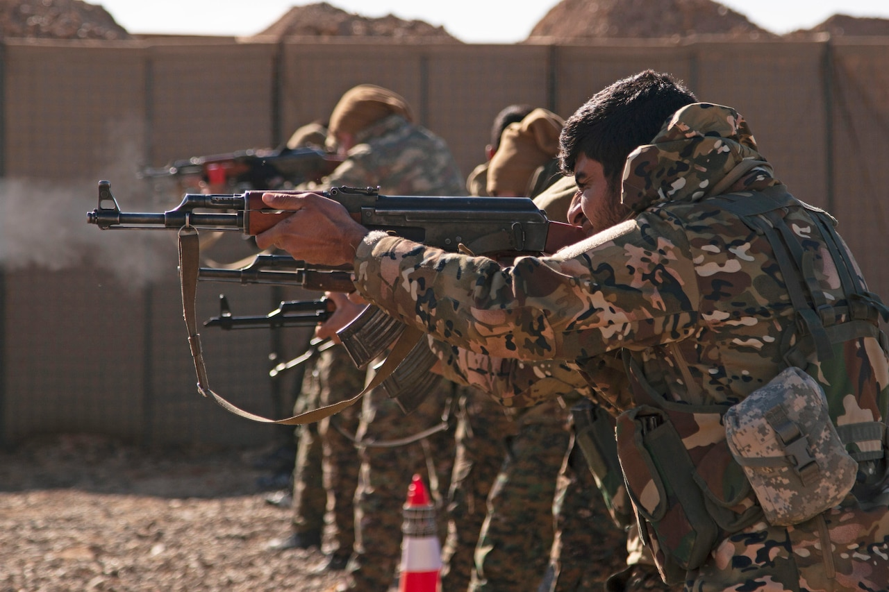 Syrian fighters fire rifles at a range.