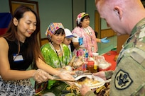 Claire Hoang, Defense Finance and Accounting Service financial management analyst, left, and Josie Swinarski, a local caterer, serve U.S. Army Sgt. Timothy Holloman, 326th Financial Management Support Center military pay technician currently assigned to the Defense Finance and Accounting Service, during an Asian American Pacific Heritage event at the Maj. Gen. Emmett J. Bean Center here June 4, 2019. The U.S. Army Financial Management Command and DFAS teamed up to host the event meant to showcase Asian and Pacific Islander heritage, whit this year's event focused specifically on South Korea and the Philippines.