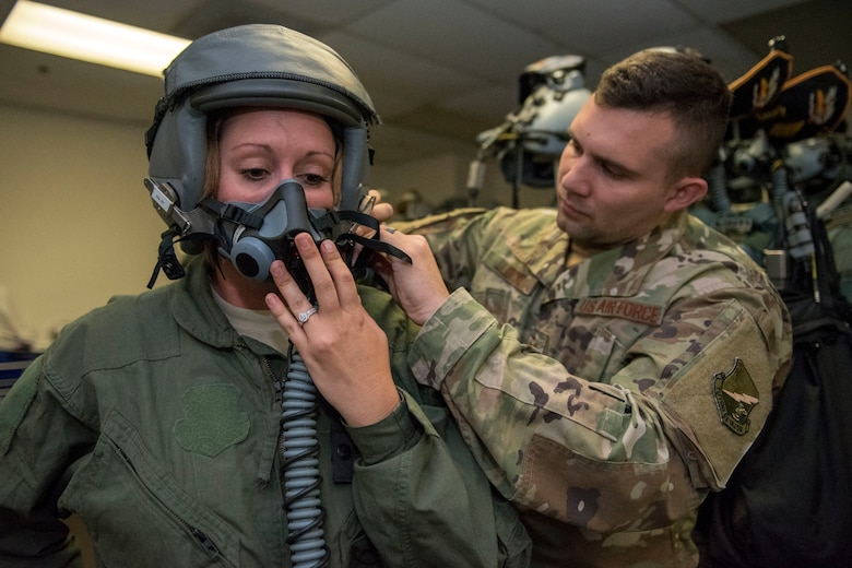 Staff Sgt. Daniel Locke, 314th Fighter Squadron Aircrew Flight Equipment technician, fits a helment to Staff Sgt. Saydee Osborn, 49th Equipment Maintenance Squadron Non-Destructive Inspection technician June 4, 2019, on Marine Corps Air Station Miramar, Calif. Airmen from the 314th FS and 314th Aircraft Maintenance Unit had the opportunity to take a familiarization flight in a 314th FS F-16 Viper to experience dissimiliar combat air training alongside F/A-18 Hornets from the Marine Fighter Attack Squadron 314. (U.S. Air Force photo by Staff Sgt. Christine Groening)