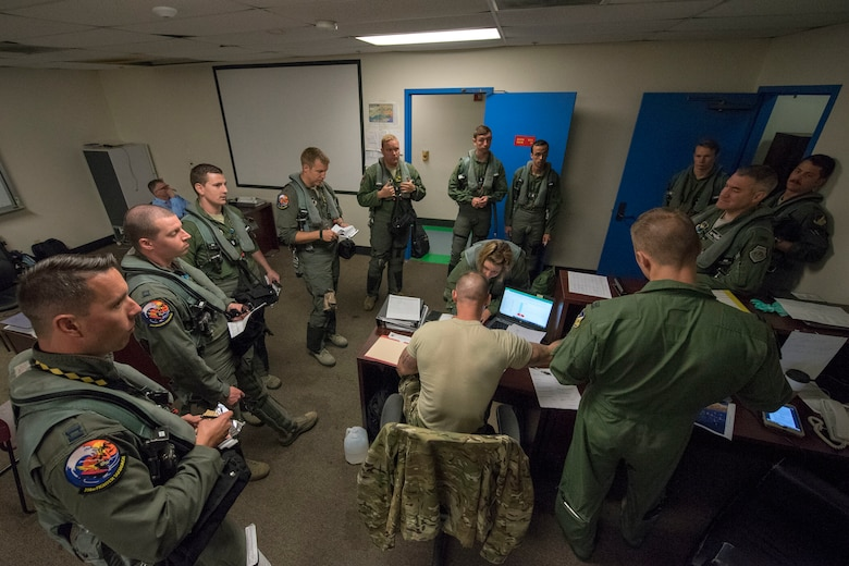 Pilots and familiarization flyers from the 314th Fighter Squadron and 314th Aircraft Maintenance Unit listen to a preflight briefing prior to stepping to the aircraft, June 4, 2019, on Marine Corps Air Station Miramar, Calif. Airmen from the 314th FS and 314th AMU had the opportunity to take familiarization flights in a 314th FS F-16 Viper to experience dissimiliar combat air training alongside F/A-18 Hornets from the Marine Fighter Attack Squadron 314. (U.S. Air Force photo by Staff Sgt. Christine Groening)