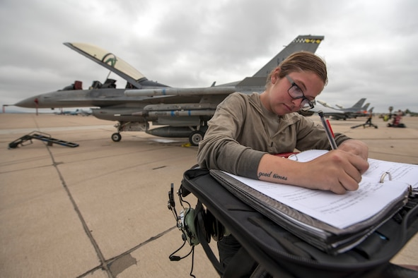Airman 1st Class Viktoria Tooker, 311th Aircraft Maintenance Unit crew chief, writes in the maintenance log book June 4, 2019, on Marine Corps Air Station Miramar, Calif. Between the 314th Fighter Squadron and the 314th AMU, 168 personnel, 16 F-16 VIpers and 14 tons of equipment were fully functional during the temporary duty assignment in support of 258 flying training sorties. (U.S. Air Force photo by Staff Sgt. Christine Groening)