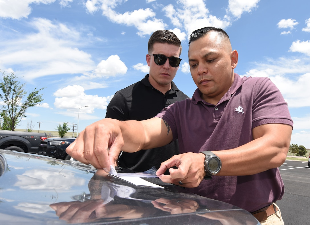 John Camacho, 50th Security Force Squadron noncommissioned officer in charge of investigations, dusts a fine powder to capture fingerprint residue left on a vehicle as investigator Kyle Maldonado, 50th SFS investigator, observes at Schriever Air Force Base, Colorado, June 5, 2019. The investigation flight provides intelligence and conducts internal security crucial to protect the base's mission and personnel. (U.S. Air Force photo by Staff Sgt. Matthew Coleman-Foster)