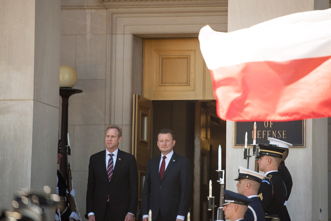 Acting Defense Secretary Patrick M. Shanahan stands with another leader at the top of a staircase flanked by service members as a Polish flag flies.