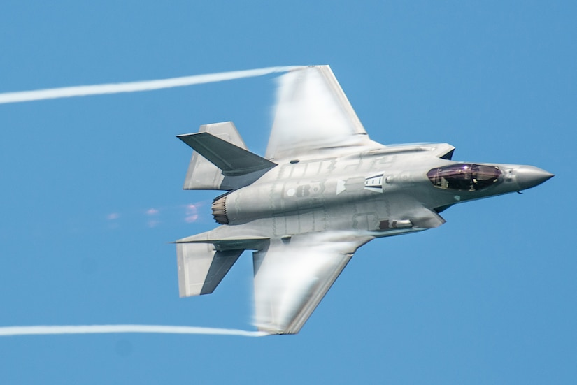 A fighter aircraft leaves trails from its wingtips against a blue sky.