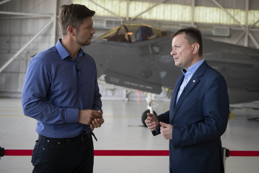 Two men speak inside an aircraft hangar with a fighter aircraft in the background.