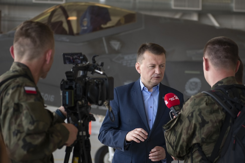 A man is interviewed on camera in an aircraft hangar with a fighter aircraft in the background.