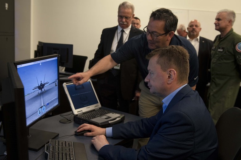 A man sits before a computer screen that is running aircraft simulation software.