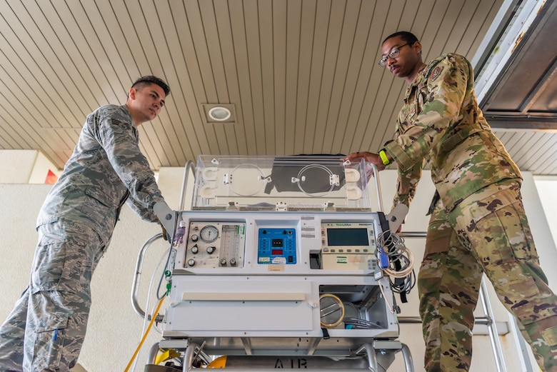 U.S. Air Force Staff Sgt. Derrik Pitchford, Critical Care Air Transport respiratory technician assigned to the 18th Aerospace Medicine Squadron, loads the neonatal transport system with Airman 1st Class Eliseo Rios, 18th AMDS aerospace medical technician, during a Neonatal Intensive Care Unit transportation course June 5, 2019, on Camp Foster, Japan. The 18th AMDS briefed the NICU nurses and technicians over the responsibilities of infant patient transportation on the ground, while the 18th AES focused on transportation while on the air. (U.S. Air Force photo by Airman 1st Class Cynthia Belío)