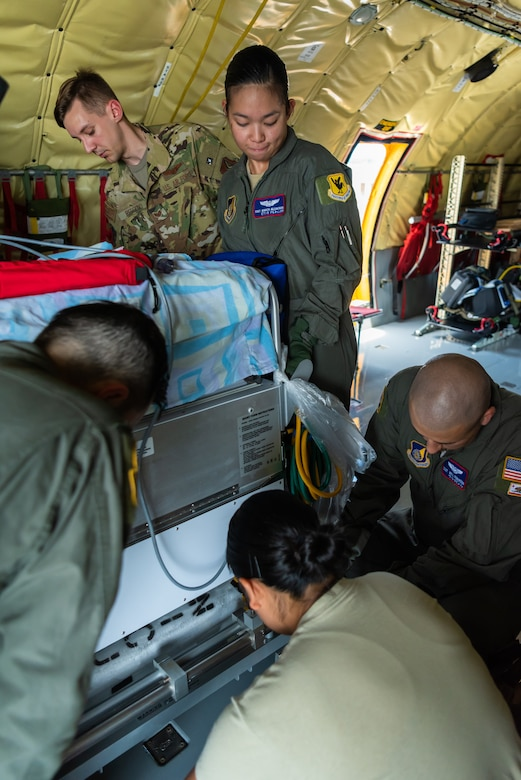 U.S. Air Force Staff Sgt. Bianca Alcantara, aeromedical evacuation technician assigned to the 18th Aeromedical Evacuation Squadron, lifts the neonatal transport system to be secured on the KC-135 Stratotanker during a Neonatal Intensive Care Unit transportation course June 5, 2019, on Kadena Air Base, Japan. The 18th Aerospace Medicine Squadron briefed the NICU nurses and technicians over the responsibilities of infant patient transportation on the ground, while the 18th AES focused on transportation while on the air. (U.S. Air Force photo by Airman 1st Class Cynthia Belío)