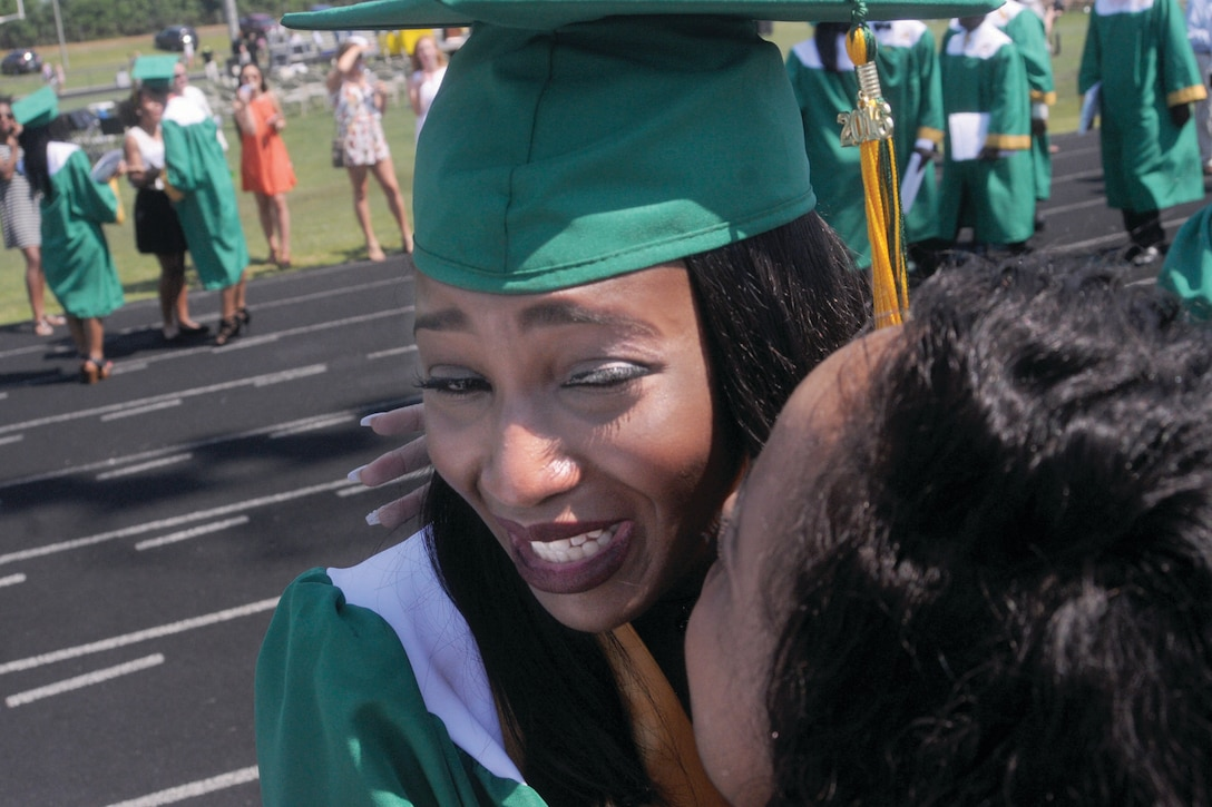 A young woman in a cap and gown hugs a woman at a graduation.