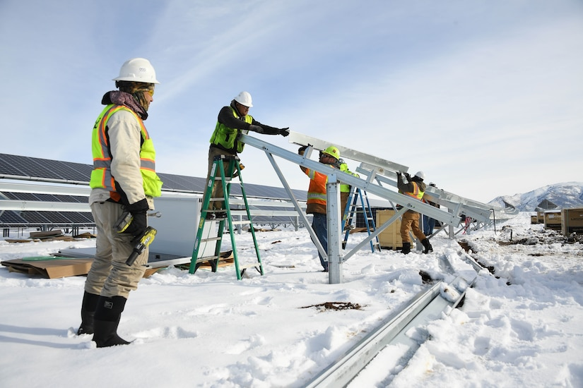 Men wearing winter clothes and hard hats install metal brackets in snowy conditions.