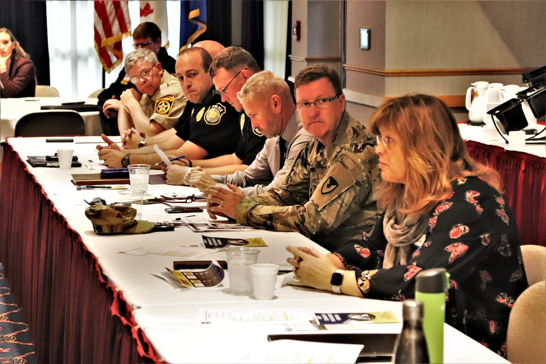 Military and civilian personnel hold a meeting at a table.