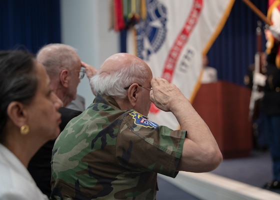 Two men salute the US flag. Woman in background.