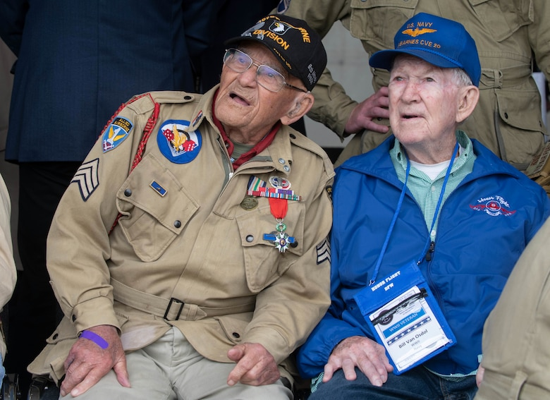 World War II veterans Robert Noody and Bill Van Osdol watch the aerial demonstration at the D-Day 75 Commemorative Airborne Operation in Sainte-Mere-Eglise, France, June 9, 2019, which honors the epic airborne operation conducted by Allied forces on June 6, 1944. This commemorative airborne operation was an opportunity for multinational forces to honor the past and simultaneously work to secure the future. Training together in the very same place that trans-Atlantic resolve began 75 years ago demonstrates the partnerships and bonds that we highly value and continue to benefit from to this day. (U.S. Air Force photo by Airman 1st Class Jennifer Zima)