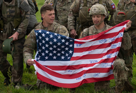 Service members hold the U.S flag after conducting a parachute jump during the D-Day 75 Commemorative Airborne Operation in Sainte-Mere-Eglise, France, June 9, 2019, which honors the epic airborne operation conducted by Allied forces on June 6, 1944. Seventy-five years later, the bravery and heroism by all allies during World War II continues to resonate with U.S. forces in Europe - who remain steadfast in their commitment to European allies and partners. (U.S. Air Force photo by Airman 1st Class Jennifer Zima)