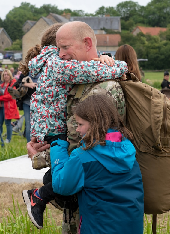 U.S. Air Force Lt. Col. Jake Miller, 752nd Special Operations Group deputy commander, embraces his daughters at the D-Day 75 Commemorative Airborne Operation in Sainte-Mere-Eglise, France, June 9, 2019. This commemorative airborne operation was an opportunity for multinational forces to honor the past and simultaneously work to secure the future. Training together in the very same place that trans-Atlantic resolve began 75 years ago demonstrates the partnerships and bonds that we highly value and continue to benefit from to this day. (U.S. Air Force photo by Airman 1st Class Jennifer Zima)