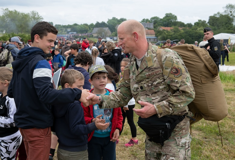 U.S. Air Force Lt. Col. Jake Miller, 752nd Special Operations Group deputy commander, greets local children at the D-Day 75 Commemorative Airborne Operation in Sainte-Mere-Eglise, France, June 9, 2019. This commemorative airborne operation was an opportunity for multinational forces to honor the past and simultaneously work to secure the future. Training together in the very same place that trans-Atlantic resolve began 75 years ago demonstrates the partnerships and bonds that we highly value and continue to benefit from to this day. (U.S. Air Force photo by Airman 1st Class Jennifer Zima)