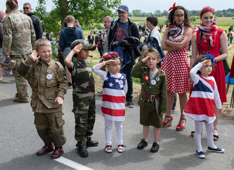 French children, dressed in mock World War II-era uniforms salute passing service members during the D-Day 75 Commemorative Airborne Operation in Sainte-Mere-Eglise, France, June 9, 2019. Seventy-five years later, the bravery and heroism by all allies during World War II continues to resonate with U.S. forces in Europe - who remain steadfast in their commitment to European allies and partners. (U.S. Air Force photo by Airman 1st Class Jennifer Zima)