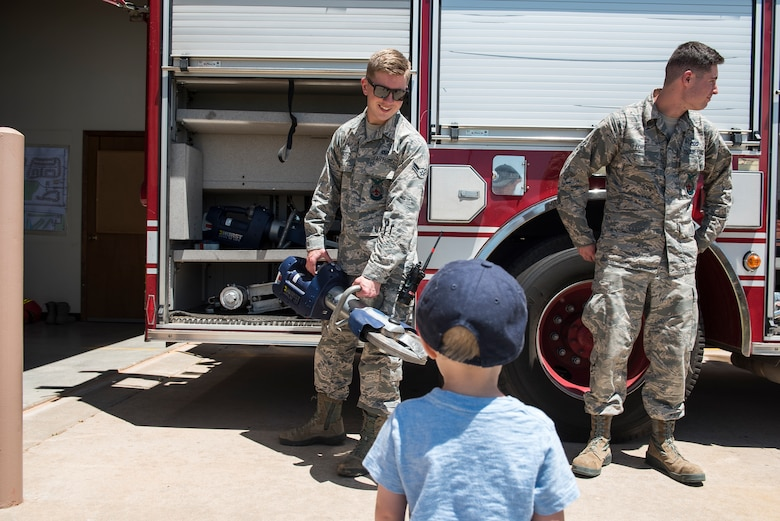 Airman 1st Class Devon Glasco, 27th Special Operations Civil Engineer Squadron firefighter, shows an open house visitor a hydraulic rescue tool at Cannon Air Force Base, N.M., June 6, 2019. Chavez housing residents were given a tour around the facility during the open house to give them a better understanding of the new station. (U.S. Air Force Photo by Airman 1st Class Vernon R. Walter III)