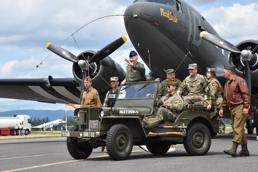 A veteran, surrounded by people, stands in a jeep that is parked on a runway in front of a World War II-era aircraft.