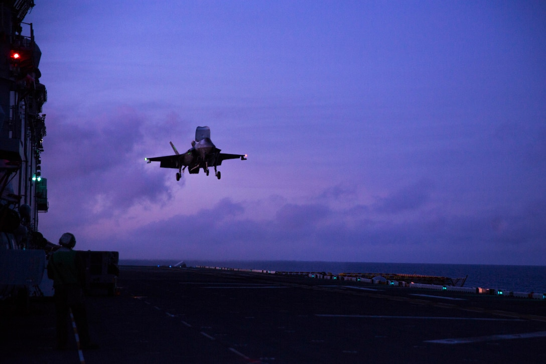 An airplane about to land on a ship's deck at night.