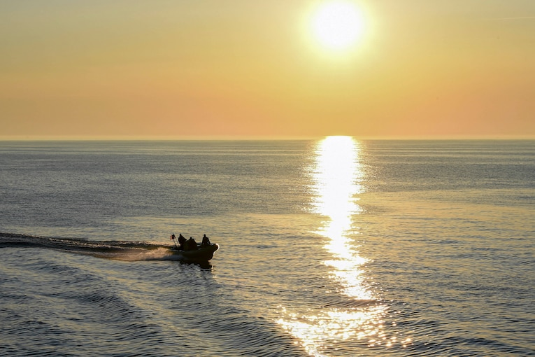 Sailors travel through waters in a small boat.