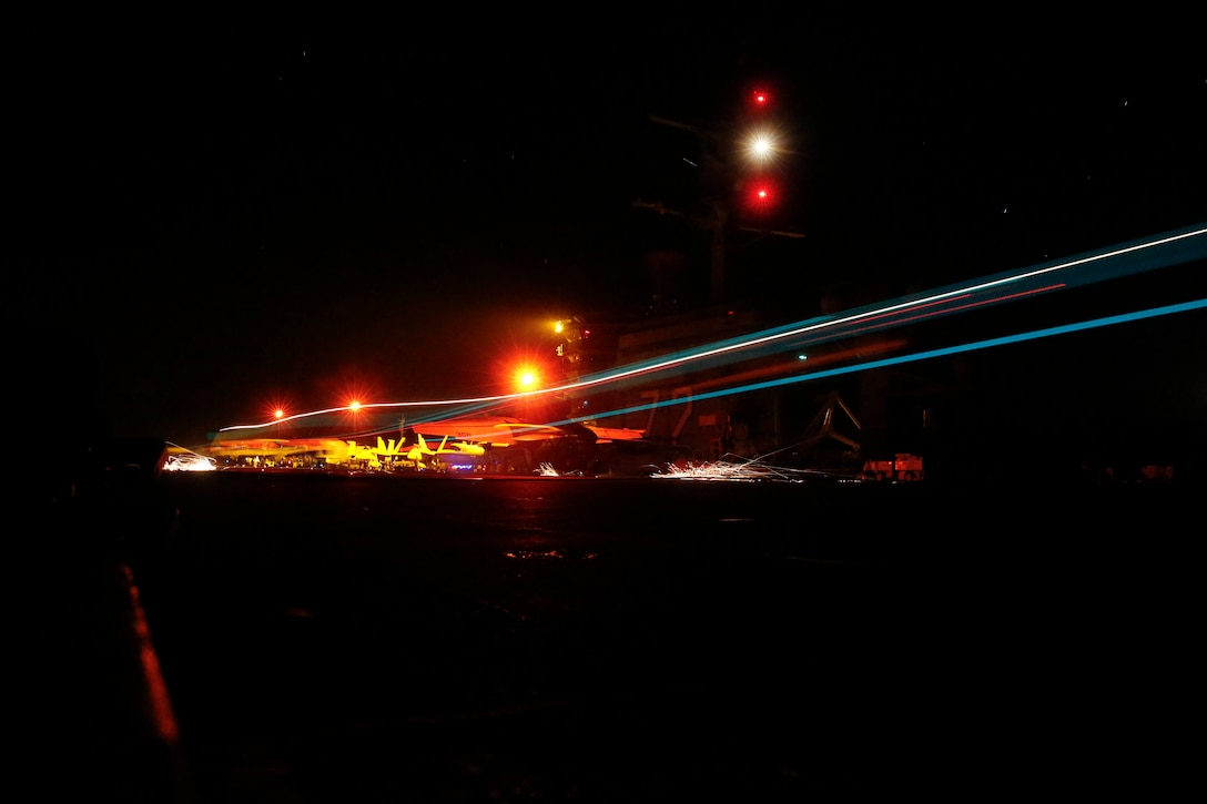 A blur of lights from a landing aircraft is shown at night on a ship's flight deck.