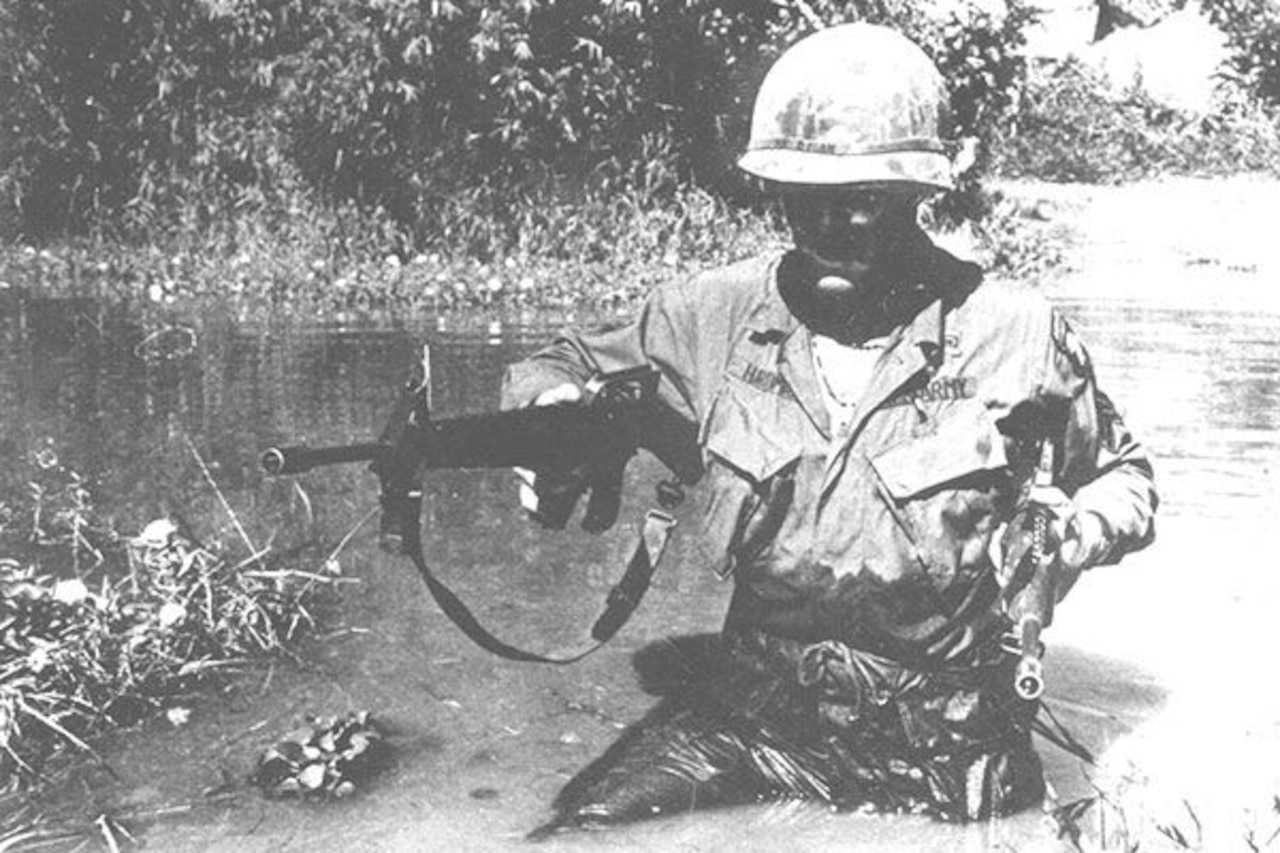 A soldier wearing battle fatigues and a helmet wades through waist-deep water in a Vietnam swamp while carrying a rifle.