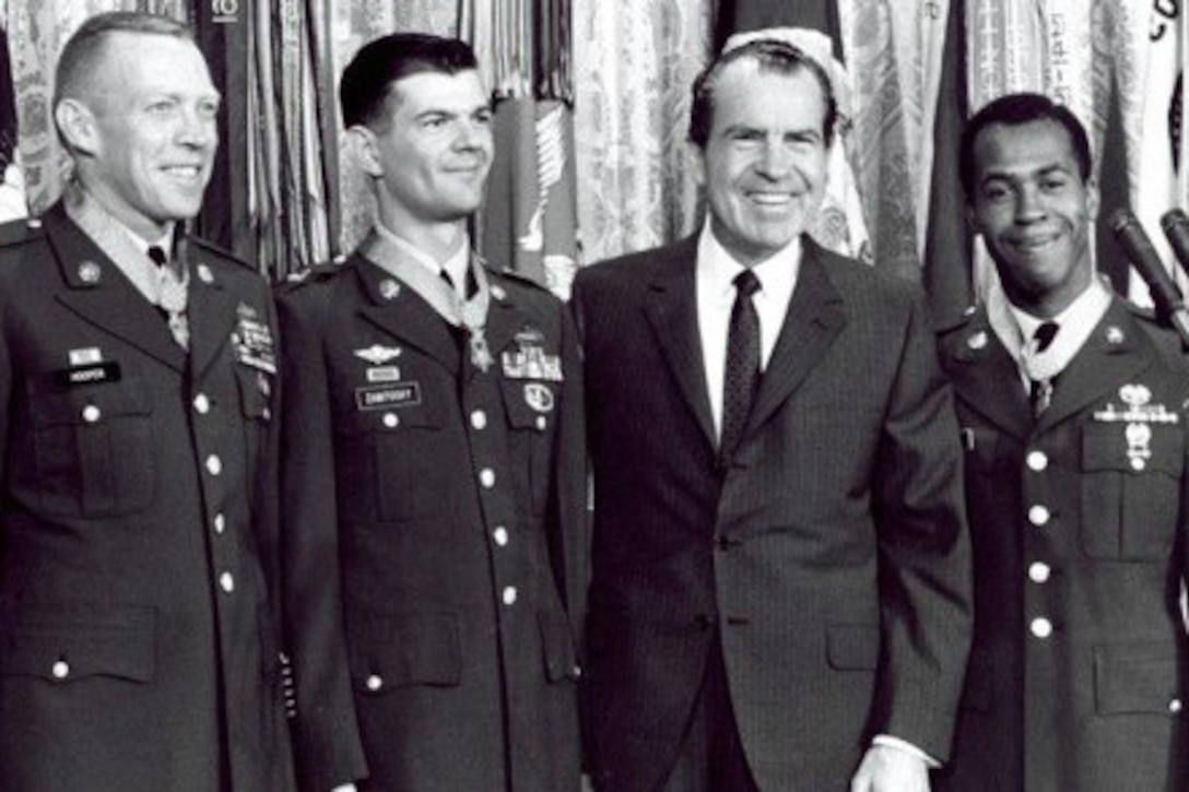 Three soldiers wearing Medals of Honor pose for a photo with President Richard Nixon.