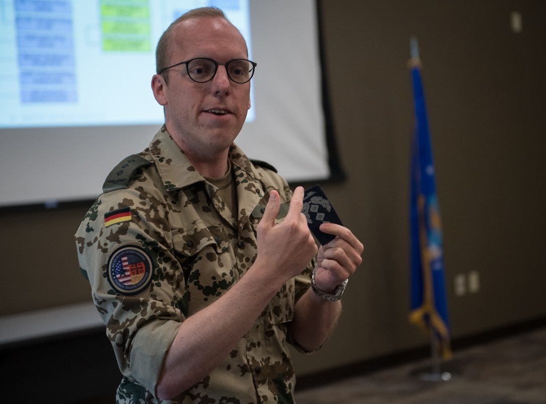 Capt. Eike Selle, officer in the German Reserve Luftwaffe (Air Force) visiting the 932nd Airlift Wing since June 1st, gives an overview of the German Reserves and some comparisons between Germany and United States to a group of Airmen from the 932nd AW,  June 12, 2019, Scott Air Force Base, Illinois. Selle shared the structure for German military rank and the various emblems.  (U.S. Air Force photo by Christopher Parr)