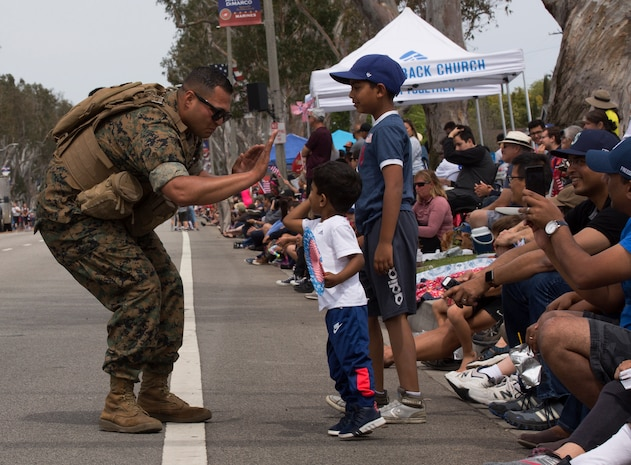 A U.S. Marine high-fives a Torrance resident during the Torrance Armed Forces Day Parade in Torrance, Calif., May 18.