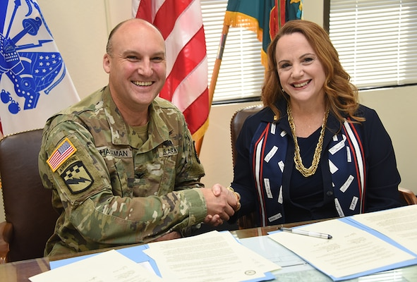 DLIFLC Commandant, Col. Gary Hausman and NSA NCS Commandant Diane M. Janosek shake hands after signing an agreement that enables U.S. service members to apply NCS completed coursework toward an Associate of Arts in Foreign Language degree from DLIFLC.