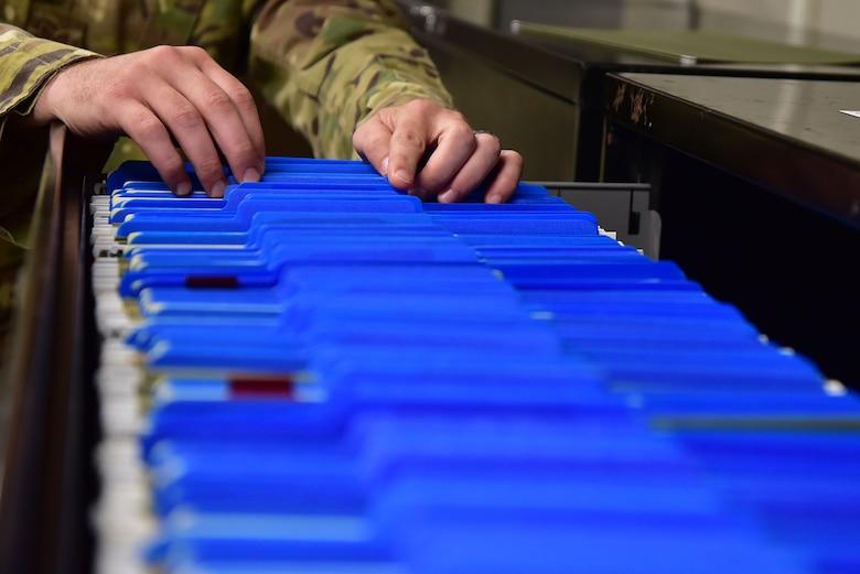 An Airman sorts through deployment folders.