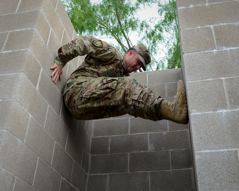 An Air Force recruiter with the 330th Recruiting Squadron practices climbing a wall following instruction from Survival, Evasion, Resistance and Escape (SERE) cadre members from 66th Training Squadron, Det. 3, at Joint Base San Antonio-Lackland June 3, 2019. Survival, Evasion, Resistance and Escape (SERE) cadre from are responsible for both the four-day Evasion and Conduct After Capture Course and the 15-day SERE Specialist Training Orientation Course at Joint Base San Antonio-Lackland. ECAC was the first stop for recruiters from the 330th RCS who travelled from across the United States to attend this biannual squadron training intended to immerse recruiters into SERE training  in order for them to be better able  to recruit Air Force SERE candidates.
