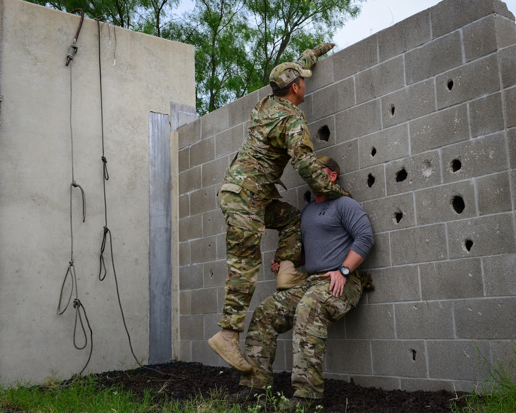 Air Force Survival, Evasion, Resistance and Escape (SERE) cadre members from 66th Training Squadron, Det. 3, at Joint Base San Antonio-Lackland demonstrate how two individuals can safely and effectively scale a wall in an evasion-type environment, June 3, 2019. Survival, Evasion, Resistance and Escape (SERE) cadre from are responsible for both the four-day Evasion and Conduct After Capture Course and the 15-day SERE Specialist Training Orientation Course at Joint Base San Antonio-Lackland. ECAC was the first stop for recruiters from the 330th RCS who travelled from across the United States to attend this biannual squadron training intended to immerse recruiters into SERE training  in order for them to be better able  to recruit Air Force SERE candidates.