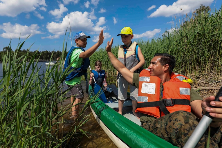 A Marine wearing a life vest in a canoe high-fives a child wading near shore as others look on.