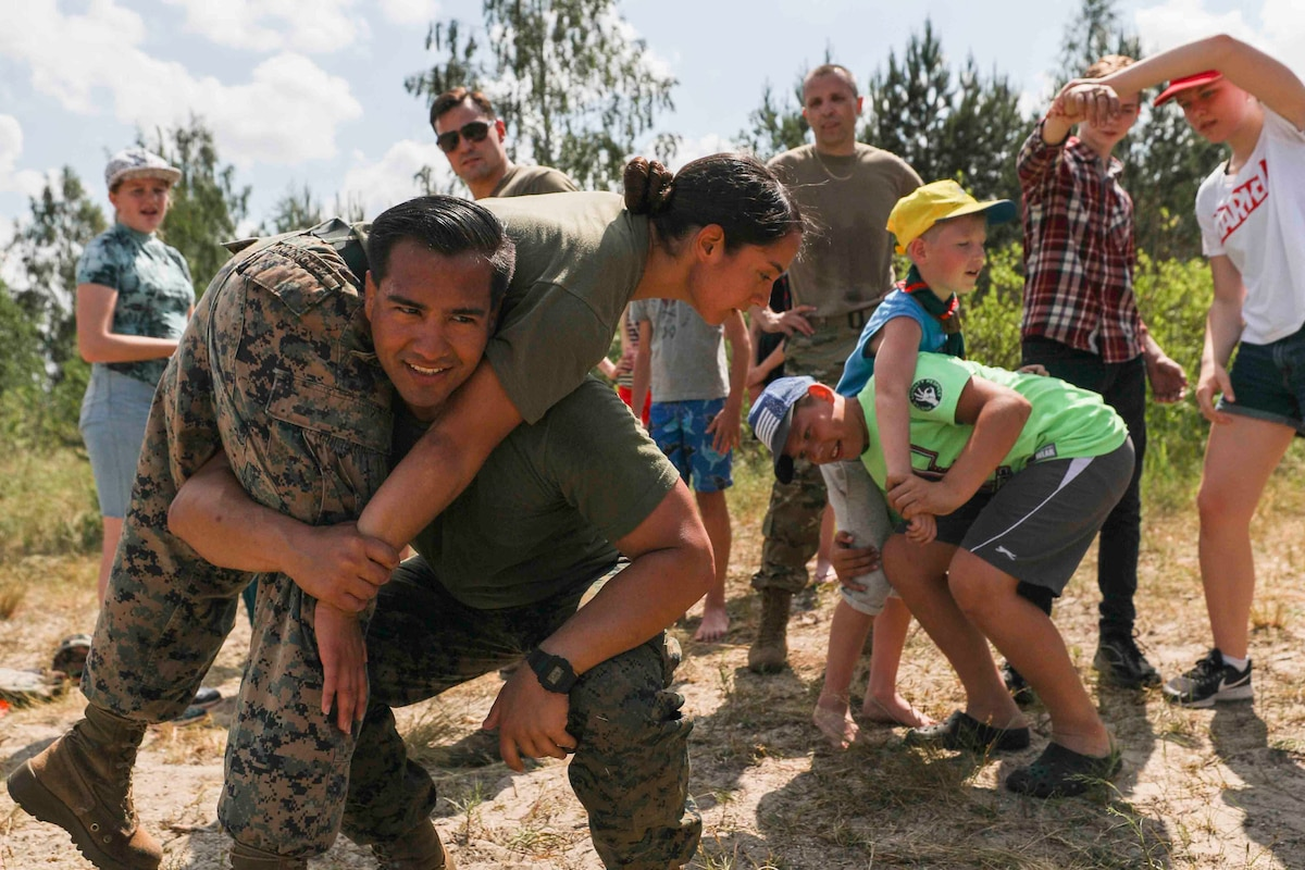 Two Marines demonstrate how to carry a person as children look on and attempt to imitate it.