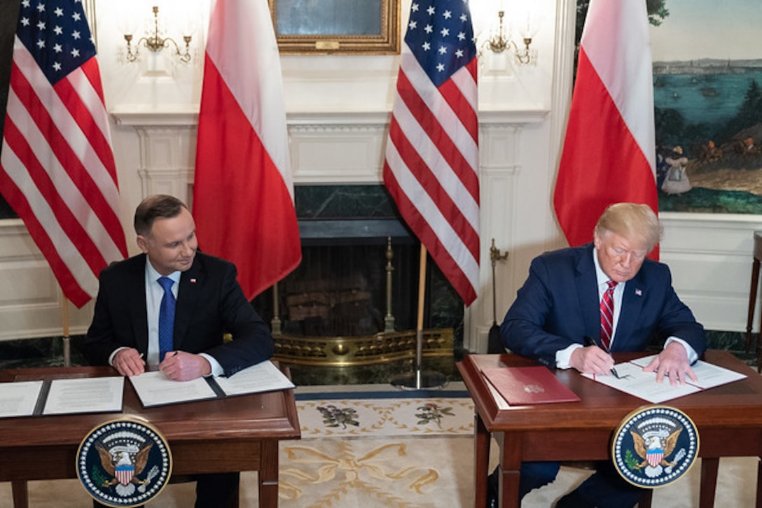 President Donald J. Trump and Polish President sit at two tables signing documents.
