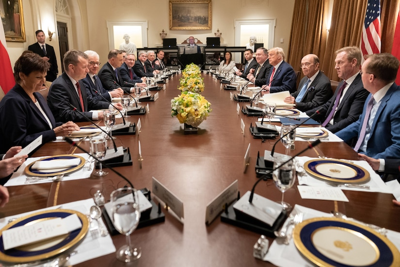 Leaders sit around a long oval table.