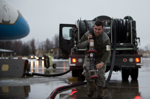 U.S. Air Force Senior Airman Aaron Dobizl, 673d Logistics Readiness Squadron, carries a fuel line while preparing to refuel Air Force Two while Vice President of the United States Mike Pence visits Joint Base Elmendorf-Richardson, Alaska, Nov. 11, 2018. The vice president is beginning a visit to Asia, and took time to visit the installation in observance of Veterans Day to meet and speak with service members and veterans of all branches.