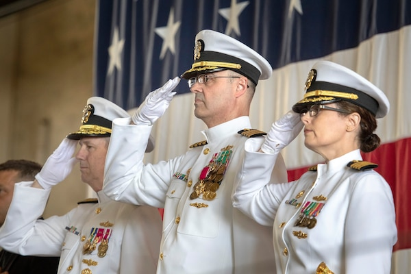 From left, Vice Adm. Thomas Moore, commander of Naval Sea Systems Command; Capt. Howard Markle, outgoing commander of Puget Sound Naval Shipyard & Intermediate Maintenance Facility; and Capt. Dianna Wolfson, incoming shipyard commander, salute the colors during the PSNS & IMF change of command ceremony June 12.