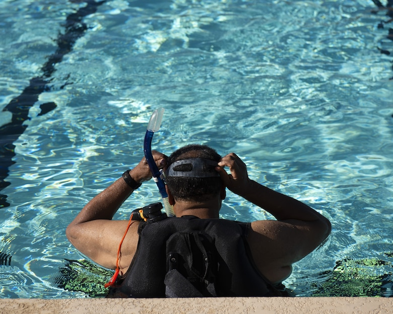 A scuba student puts his goggles and snorkel in place before swimming June 8, 2019, at Luke Air Force Base, Ariz.