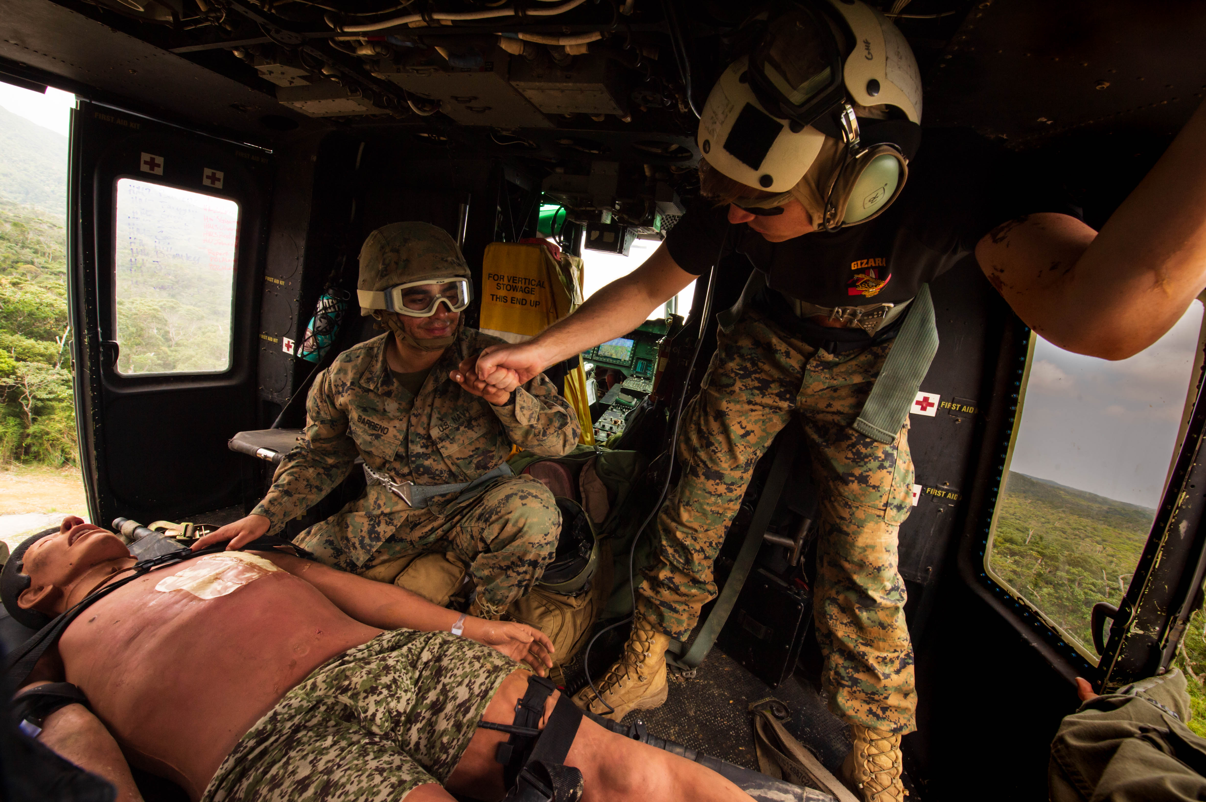Sailors provide medical care to a mannequin on a helicopter.