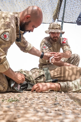 Canadian soldiers Master Cpl. Marc Deschesnes, left, and Cpl. Dave Lucas, assigned to the Qayyarah West Canadian Training Team, demonstrate the proper procedure for treating a chest wound to Iraqi provincial police members on Qayyarah West Airfield, Iraq, May 19, 2019. Iraqi students go through a four-week Wide Area Security Forces class taught by Canadian soldiers to learn essential combat skills like first aid, tactical movement, urban operations, and detainee procedures to enhance the Iraqi Security Forces' combat skills and self-sufficiency. Coalition Forces are in Iraq at the invitation of the Government of Iraq to train and advise in support of the enduring mission to defeat Daesh. (U.S. Army Reserve photo by Spc. DeAndre Pierce)