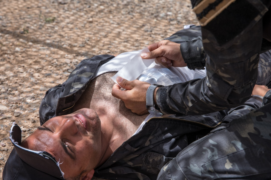 An Iraqi provincial police member assigned to the 4th Ninawa Emergency Response Battalion tapes down a chest seal during a combat first aid class on Qayyarah West Airfield, Iraq, May 19, 2019. Iraqi students go through a four-week Wide Area Security Forces class taught by Canadian soldiers to learn essential combat skills like first aid, tactical movement, urban operations, and detainee procedures to enhance the Iraqi Security Forces' combat skills and self-sufficiency. Coalition Forces are in Iraq at the invitation of the Government of Iraq to train and advise in support of the enduring mission to defeat Daesh. (U.S. Army Reserve photo by Spc. DeAndre Pierce)
