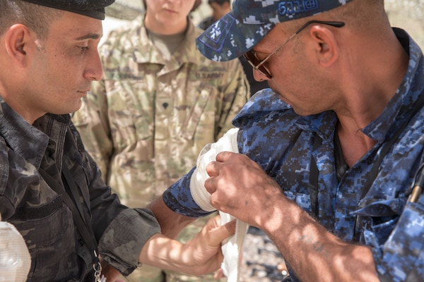 Iraqi provincial police members assigned to the 4th Ninawa Emergency Response Battalion apply a bandage during a combat first aid class on Qayyarah West Airfield, Iraq, May 19, 2019. Iraqi students go through a four-week Wide Area Security Forces class taught by Canadian soldiers to learn essential combat skills like first aid, tactical movement, urban operations, and detainee procedures to enhance the Iraqi Security Forces' combat skills and self-sufficiency. Coalition Forces are in Iraq at the invitation of the Government of Iraq to train and advise in support of the enduring mission to defeat Daesh. (U.S. Army Reserve photo by Spc. DeAndre Pierce)