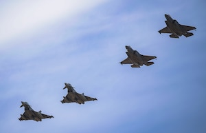 Two F-35A Lightning II aircraft seen flying in formation with NATO allied aircraft.