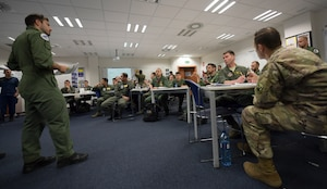 U.S. and NATO pilots review and discuss flight plans during a pre-flight briefing.