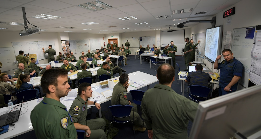 Group of U.S. and NATO pilots seen in pre-flight briefing room.